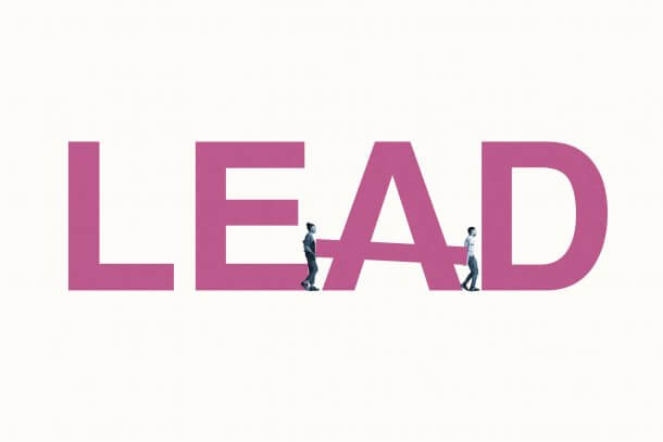 Full length side view of young man and woman building LEAD word against white background