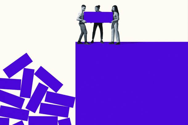Full length of young friends throwing purple blocks from cliff against white background