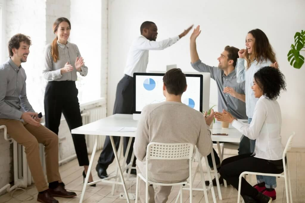 group of happy people looking at computer with marketing report