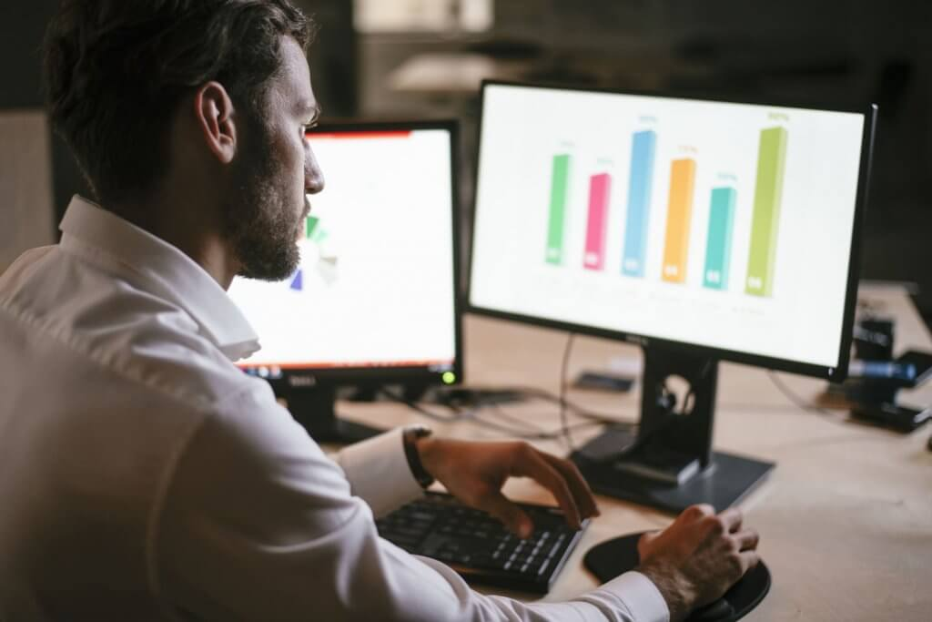 man looking into computer with chart